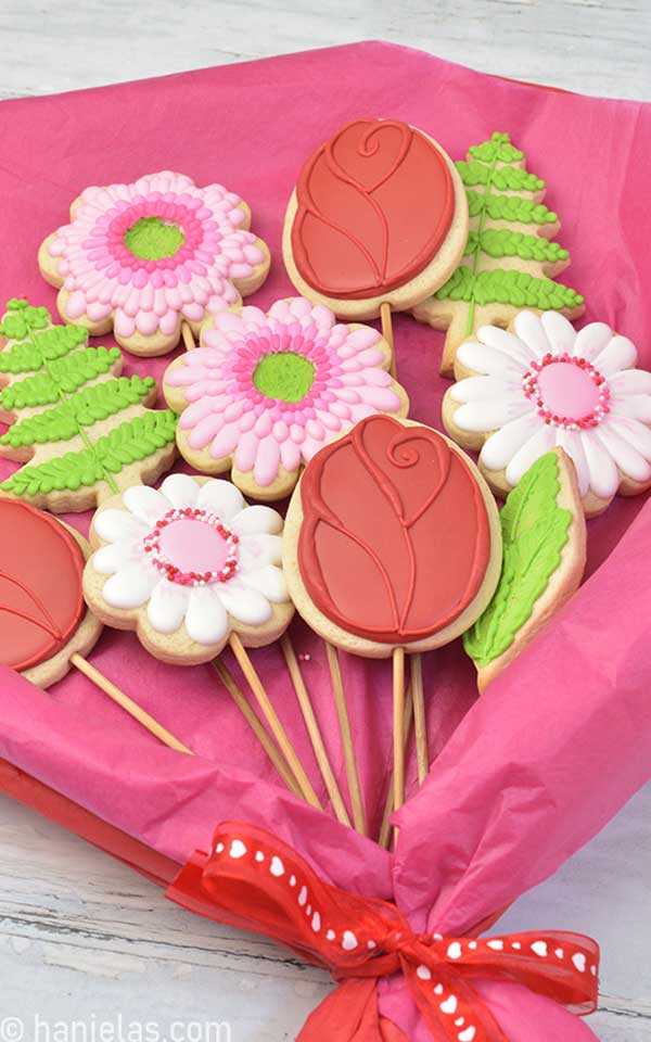 Decorated flower cookies on bamboo sticks arranged into a flower bouquet.