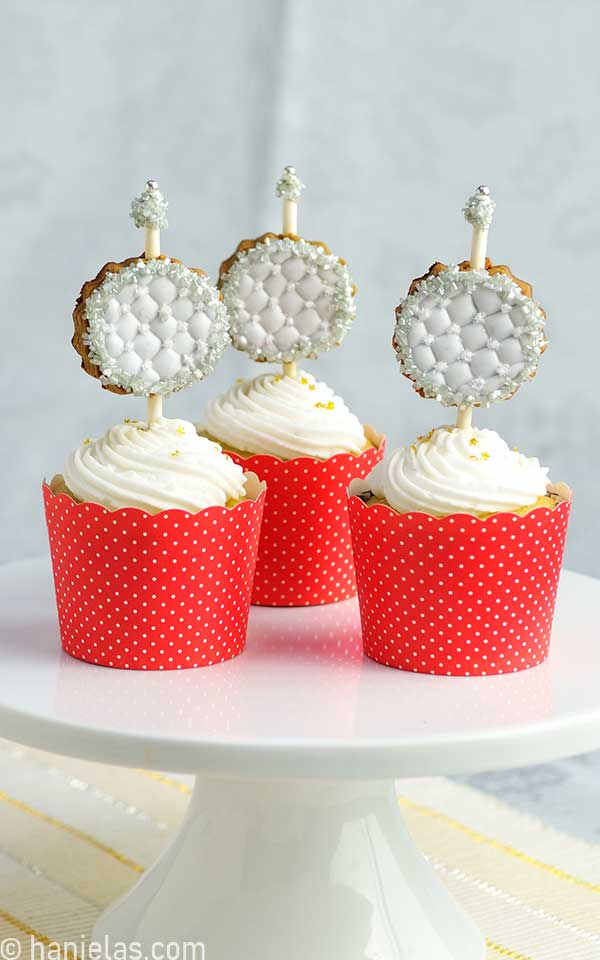 Cupcakes in red liners with a white buttercream on a cake stand.