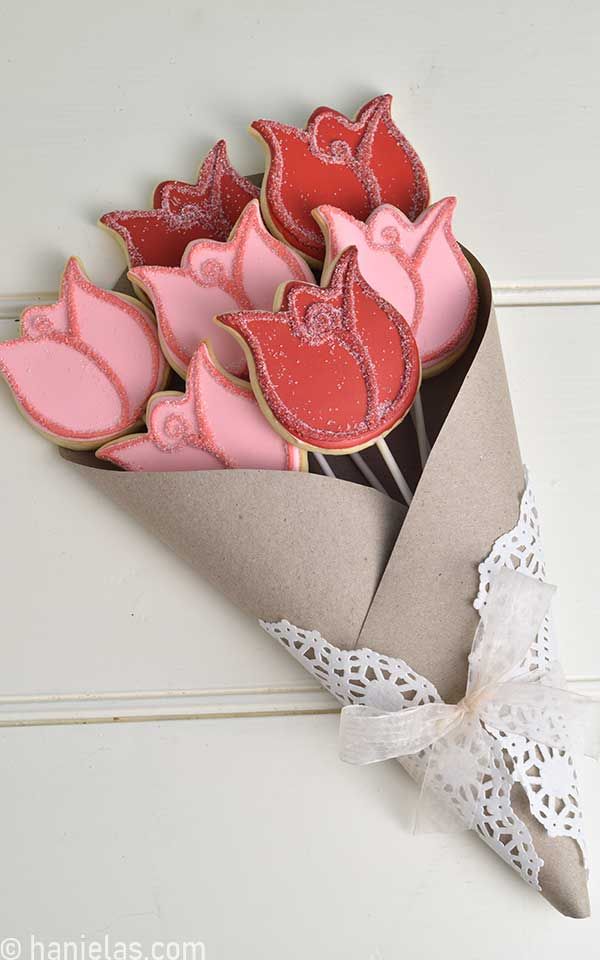 Decorated rose cookies wrapped in a brown craft paper and white doily.