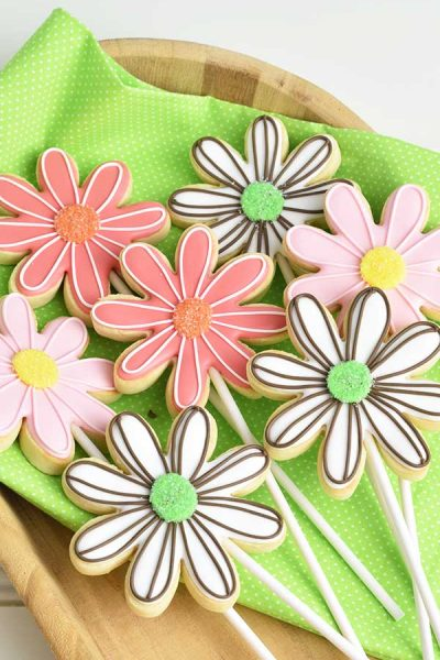 Decorated daisy flower cookies on a wood tray lined with bright green cloth.
