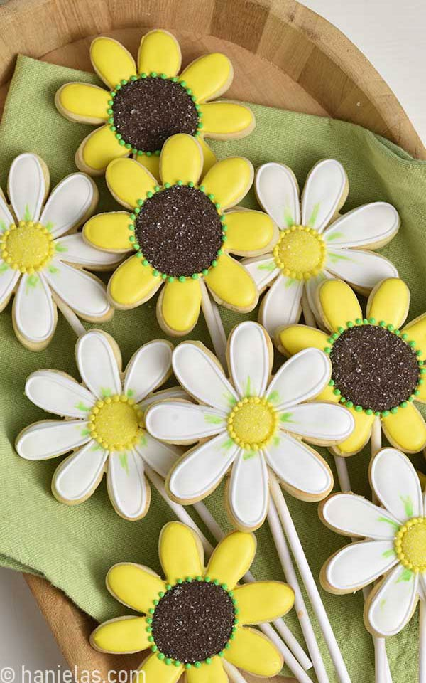 Yellow and white decorated daisy cookies on a wooden tray lined with green napkin.