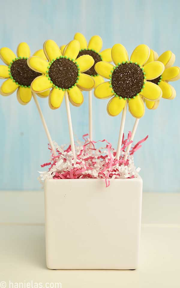 Sunflower cookies on a stick displayed in a white vase.