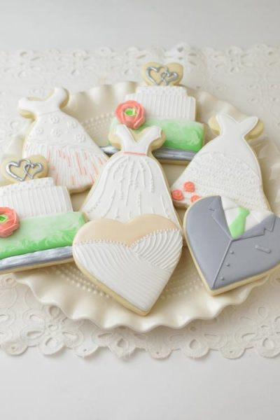 Groom and bride heart , wedding cake and bridal dress cookies on a plate.