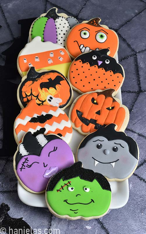 Decorated pumpkin shaped cookies on a white plate.