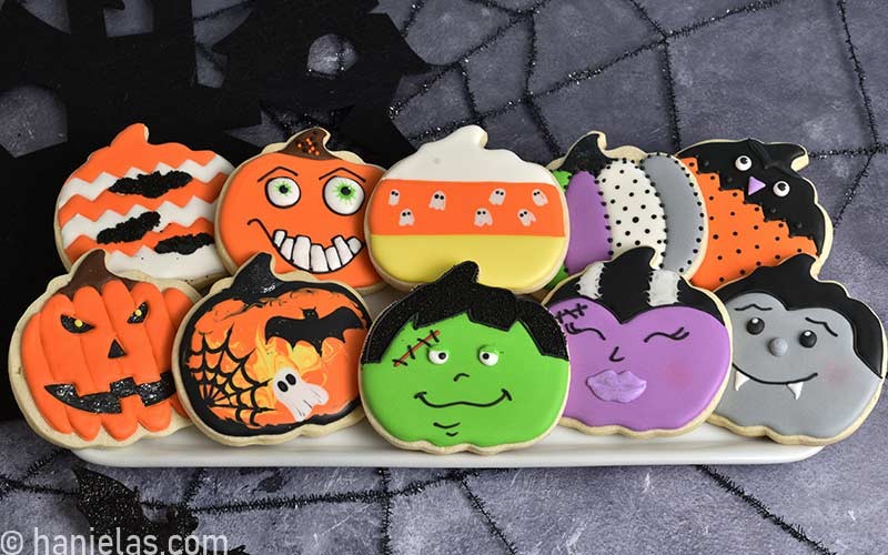 Decorated pumpkin Halloween cookies displayed on white rectangular plate.