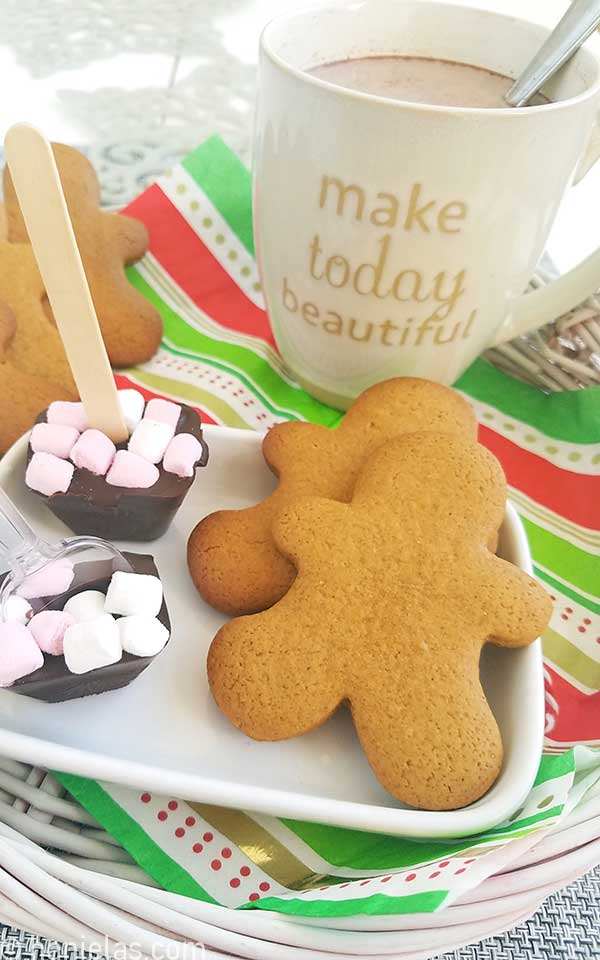 Baked gingerbread men cookies on a white plate with hot chocolate.