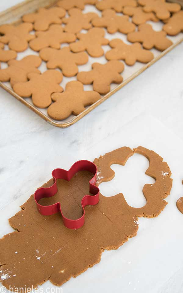 Rolled out cookie dough with a gingerbread men cookie cutter on the top.