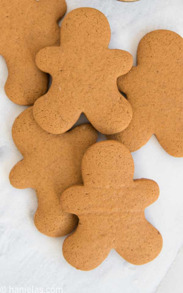 Baked gingerbread men cookies, undecorated stacked on a white background.