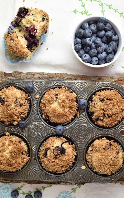 Baked muffins in a pretty muffin tin, fresh blueberries in small bowl.