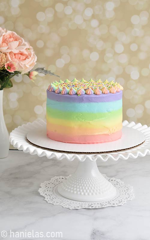 Rainbow frosted cake displayed on milk glass cake stand.