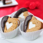 Heart s'mores sandwiches nested in paper liners.