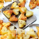 Roasted potatoes on a metal spatula.