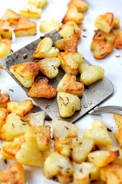 Roasted potatoes on a metal spatula.