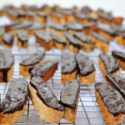 Cookies dipped in chocolate on a cooling rack.