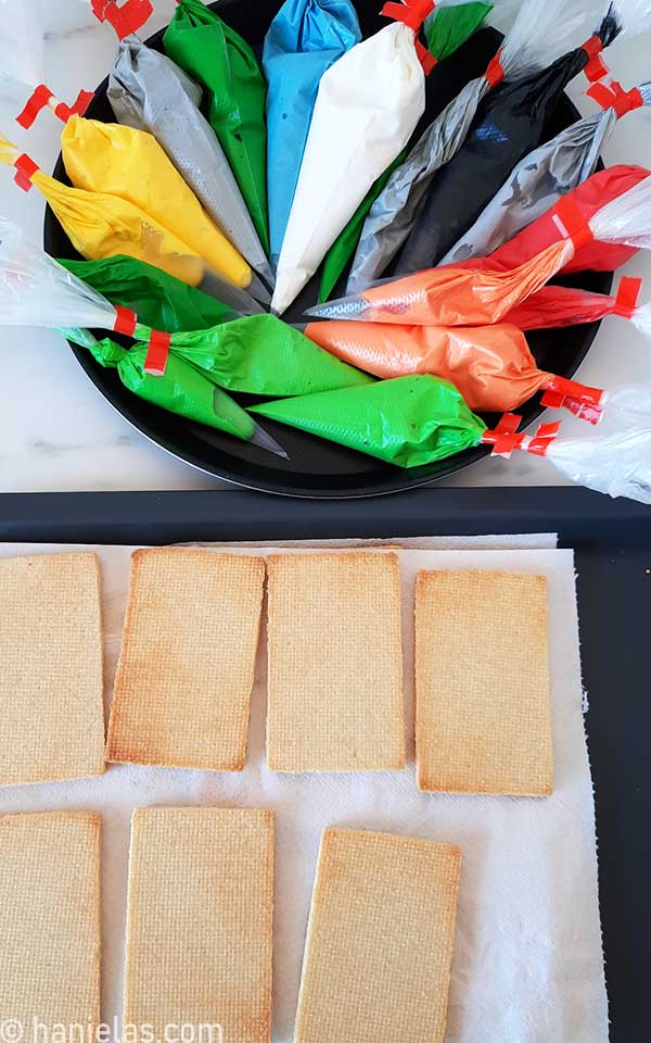 Rectangular cookies on a paper towel, and piping bags filled with royal icing.