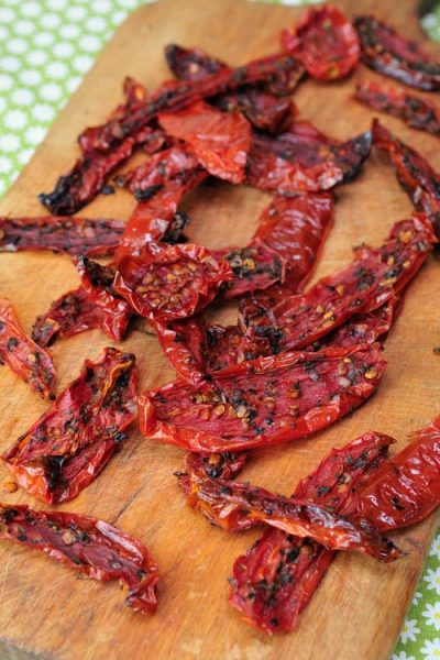 Dried roma tomatoes slices on a cutting board.