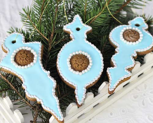 Christmas ornament cookies displayed on a green pine branch.