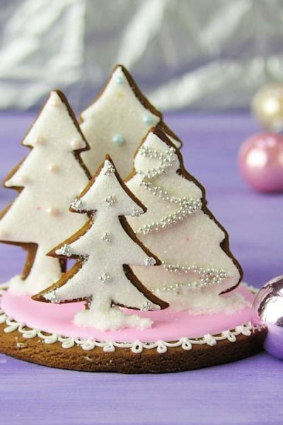 Tree cookies decorated with white icing glued on a round base standing up.