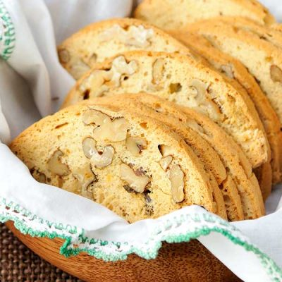 Golden yellow baked and sliced cookies a basket lined with white napkin.