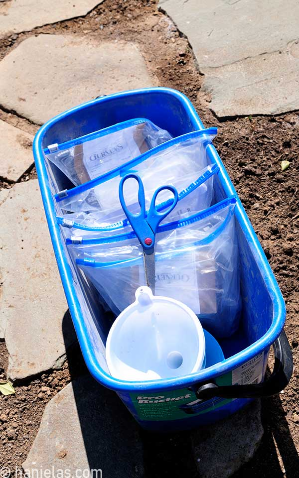 Blue bucket with packets of seeds inside of plastic bags..