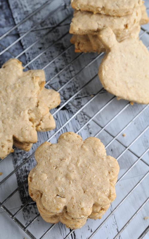 Cut out flower shaped oatmeal sugar cookies on a cooling rack