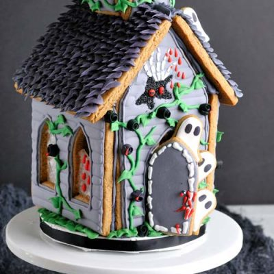 Decorated gingerbread house on a white cake stand.