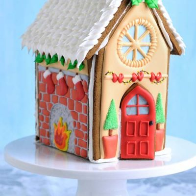 Decorated gingerbread house displayed on white round cake stand.