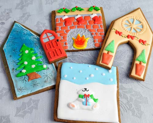Decorated gingerbread house panels displayed flat on a table.