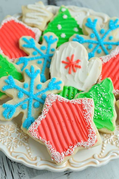 Cookies decorated with buttercream on a pretty festive plate.