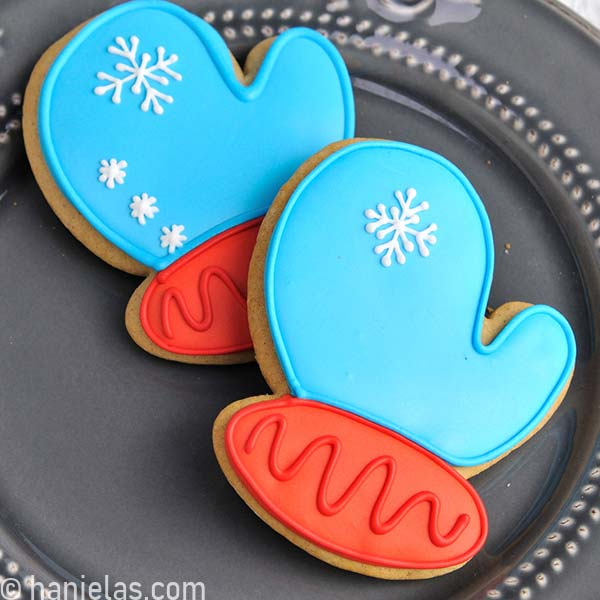 Mitten cookie decorated with blue and red icing on a gray plate.