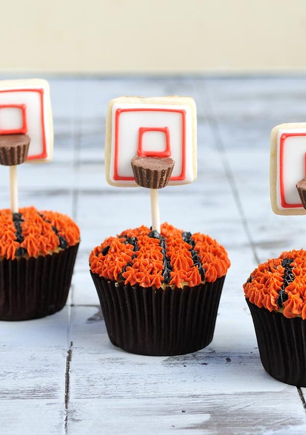 Cupcakes in brown liners decorated with buttercream and cookie pops.