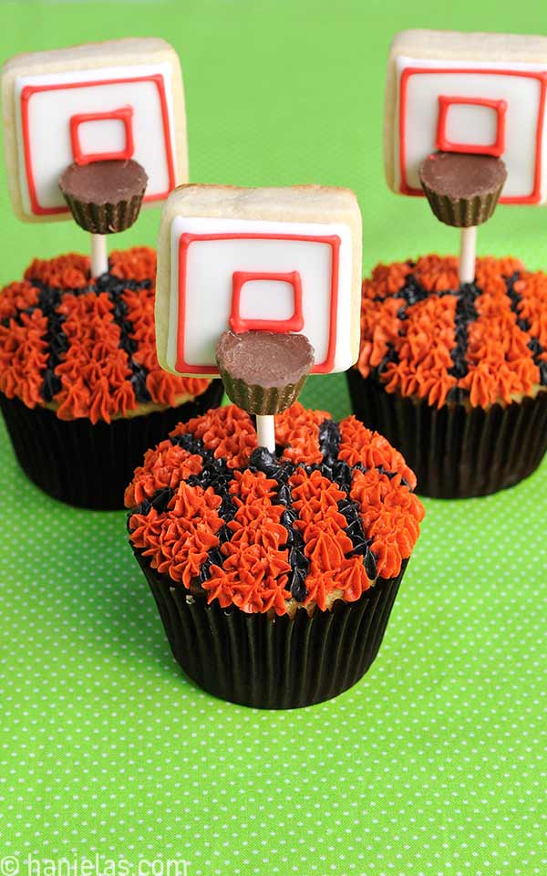 Cupcakes decorated with black and orange buttercream that look like basketballs with a cookie pop inserted in them, displayed on a green cloth.