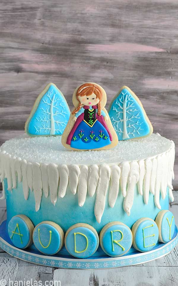 Blue winter style cake decorated with cookie pops toppers.
