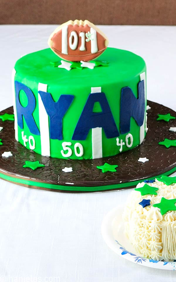 Green football style cake decorated with brown football cookie pop.