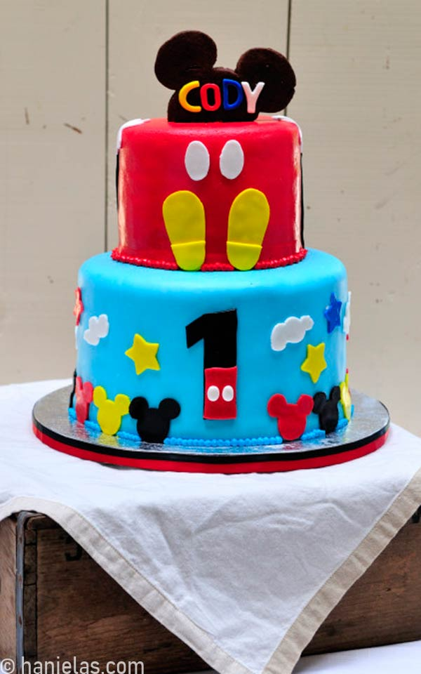 Cake decorated with Mickey Mouse ears cookie on a strick.