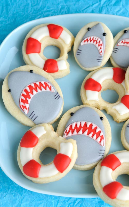 Decorated shark cookies and lifebuoy cookies on a plate.
