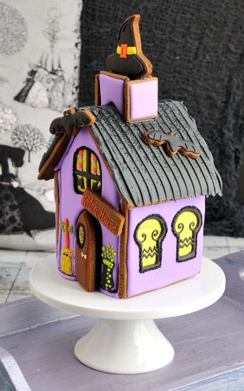 Decorated gingerbread house on a cake stand.