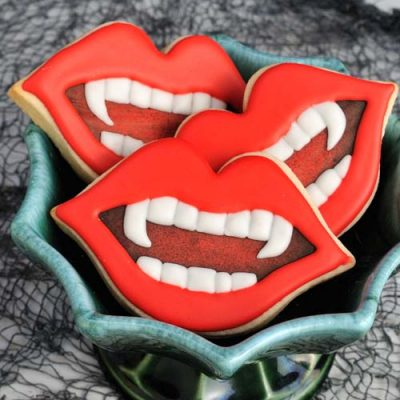 Vampire teeth decorated sugar cookies in a bowl.