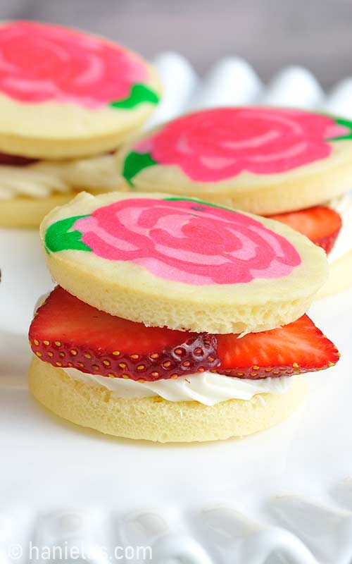Small sponge cake filled with cream cheese frosting and sliced strawberries.