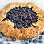 Baked blueberry galette on a parchment paper.
