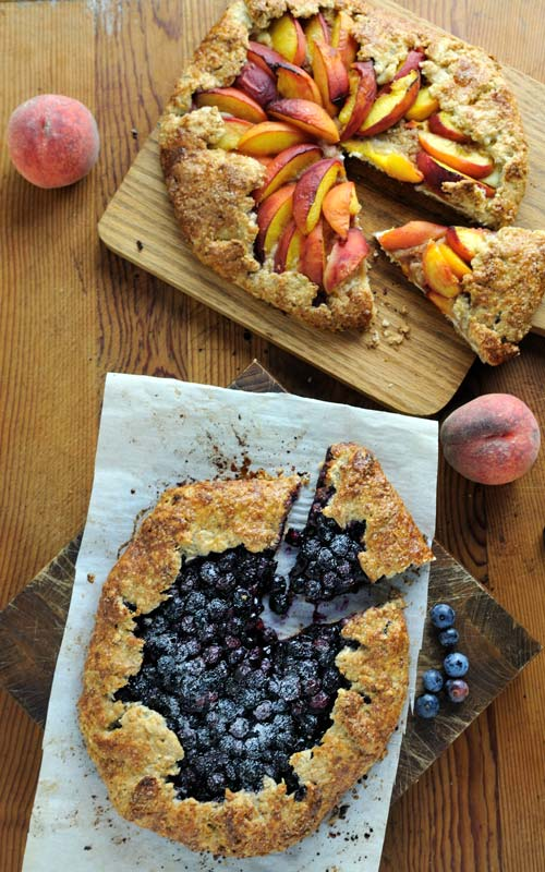 Sliced peach and blueberry free form tarts on wooden cutting boards..