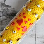 Cake roll decorated with fondant bees and heart.