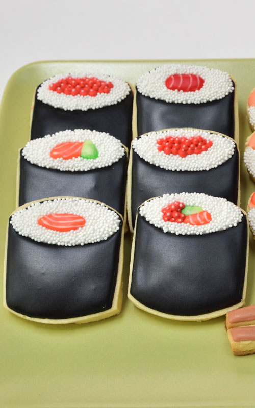 Sushi roll cookies decorated with royal icing displayed a plate.