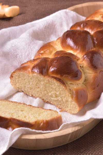 Challah bread loaf on a kitchen towel.