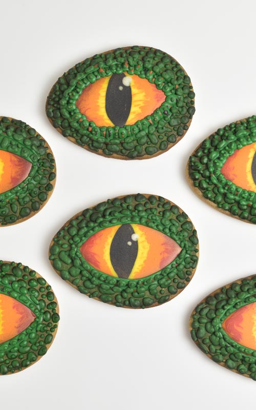 Cookies decorated with royal icing that look like dinosaur eyes displayed on a white background.
