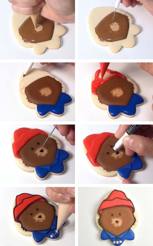 With royal icing piping a nose and a read hat on a bear cookie. Drawing facial details on dry royal icing with an edible marker.