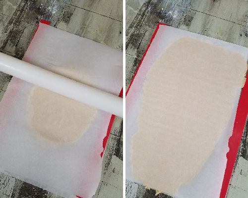 Cookie dough rolled out between parchment paper