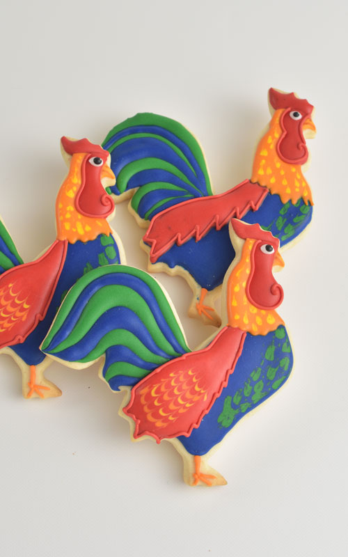 Colorful rooster cookies decorated with royal icing
