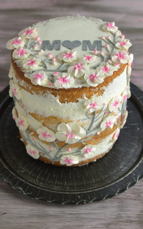 cake decorated with cherry blossom buttercream flowers