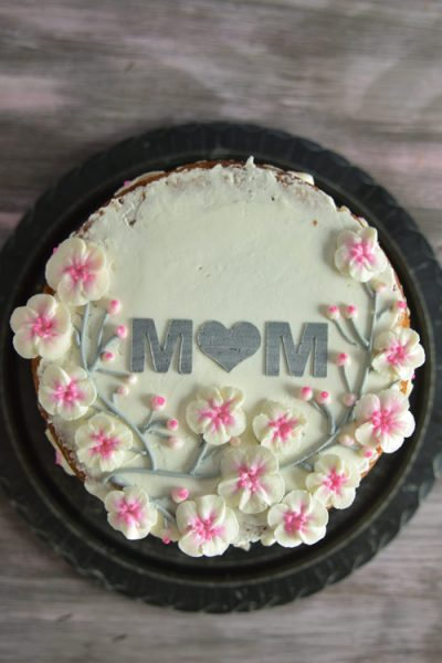 Mother's day cake decorated with buttercream cherry blossoms flowers.